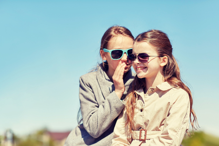 young lady: people, children and friendship concept - happy little girl in sunglasses whispering her secret to friends ear or gossiping outdoors
