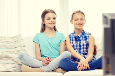 watching: people, children, television, friends and friendship concept - two happy little girls watching tv at home