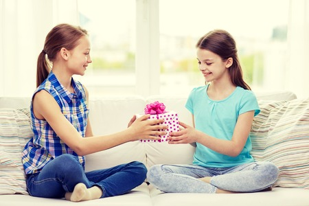 receiving: people, children, holidays, friends and friendship concept - happy little girls with birthday present sitting on sofa at home