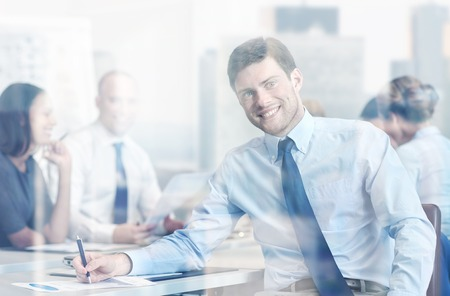 group meeting: business, people and teamwork concept - smiling businessman with group of businesspeople meeting in office Stock Photo