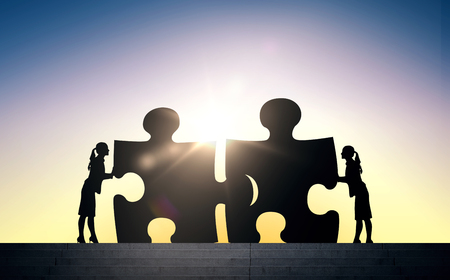 people development: business, strategy, startup, development and people concept - silhouette of two business women connecting puzzle pieces over sun light background