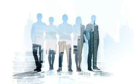 het bedrijfsleven, teamwork en mensen concept - mensen uit het bedrijfsleven silhouetten op stad achtergrond met dubbele belichting effect Stockfoto