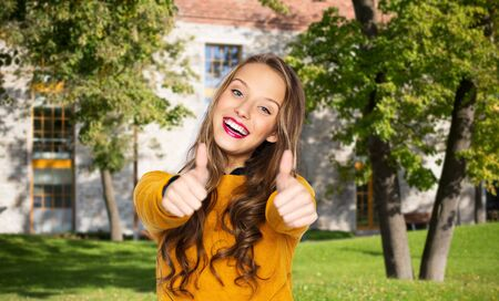 people, gesture, education and fashion concept - happy young woman or teen girl in casual clothes showing thumbs up over campus and summer park background Stock Photo