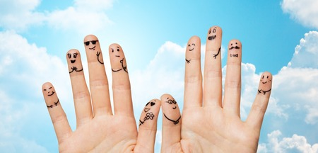 celebration smiley: gesture, family, wedding, people and body parts concept - close up of two hands showing fingers with smiley faces over blue sky and clouds background