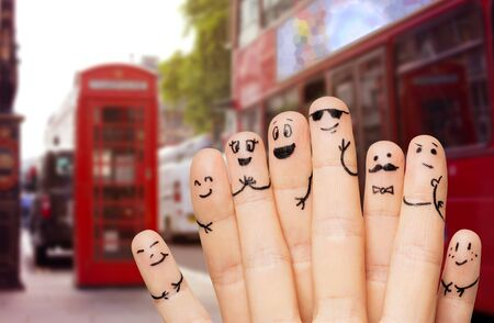 britain: travel, tourism, family, people and body parts concept - close up of two hands showing fingers with smiley faces over london city street and red bus background