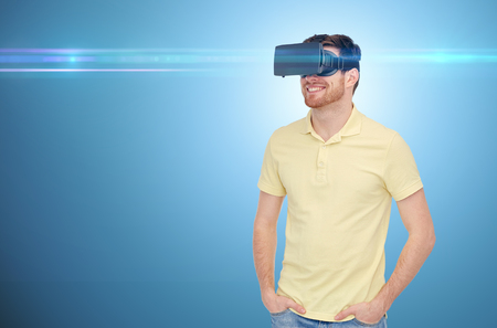 mediated: 3d technology, virtual reality, entertainment and people concept - happy young man with virtual reality headset or 3d glasses over blue background and laser light