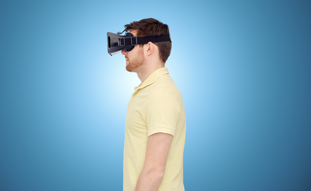 mediated: 3d technology, virtual reality, entertainment and people concept - young man with virtual reality headset or 3d glasses over blue background Stock Photo