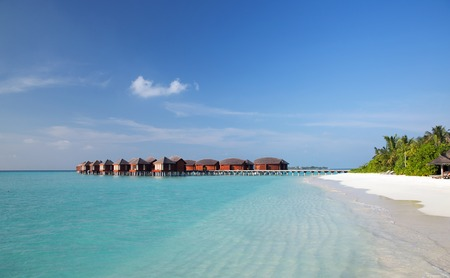 bungalow: travel, tourism, vacation and summer holidays concept - bungalow huts in sea water on exotic resort beach