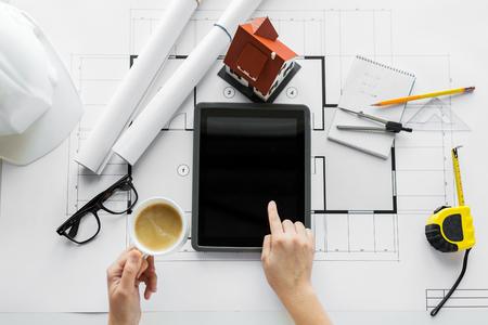 negocio, arquitectura, construcción, construcción y concepto de la gente - cerca de la mano del arquitecto con vivir plano de una casa y un ordenador Tablet PC