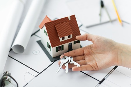 building estate: architecture, building, construction, real estate and home concept - hand with house keys and blueprint