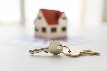 hypotheek, investering, onroerend goed en eigendom concept - close-up van huis model, geld en huis sleutels Stockfoto