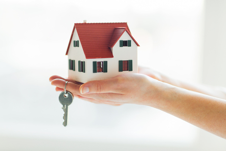 private parts: building, mortgage, real estate and property concept - close up of hands holding house model and home keys