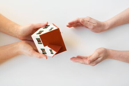 receiving: charity, building, sale, real estate and property concept - close up of hands giving and receiving house or home model Stock Photo
