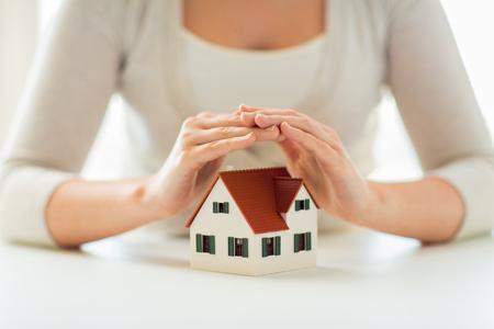 architectuur, veiligheid, beveiliging, onroerend goed en onroerend goed concept - close-up van de handen te beschermen huis of thuis model