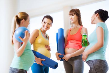 Schwangerschaft, Sport, Fitness, Menschen und gesunden Lifestyle-Konzept - Gruppe von glücklichen schwangeren Frauen mit Sportgeräten in der Turnhalle im Gespräch