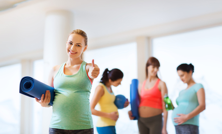 pregnancy, sport, fitness, people and healthy lifestyle concept - happy pregnant woman with mat in gym showing thumbs up