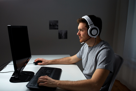 technology, gaming, entertainment, let's play and people concept - young man in headset with pc computer playing game at home and streaming playthrough or walkthrough video Reklamní fotografie