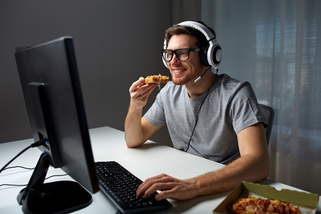 technology, gaming, entertainment, lets play and people concept - happy young man in headset with pc computer eating pizza while playing game at home and streaming playthrough or walkthrough video Stock Photo