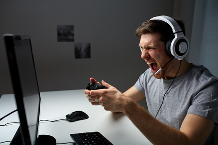 technology, gaming, entertainment, lets play and people concept - angry screaming young man in headset with controller gamepad playing computer game at home and streaming playthrough video
