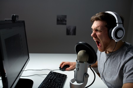 computer gaming: technology, gaming, entertainment, lets play and people concept - angry screaming young man in headset with pc computer playing game at home and streaming playthrough or walkthrough video