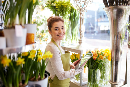 people, business, technology, sale and floristry and concept - happy smiling florist woman with tablet pc computer at flower shop 免版税图像 - 61136712