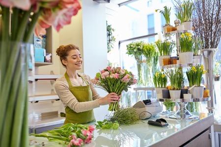 mensen, het bedrijfsleven, de verkoop en bloemisterij concept - gelukkig lachende bloemist vrouw die bos in bloemenwinkel