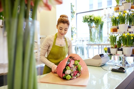 people, business, sale and floristry concept - happy smiling florist woman wrapping bunch into paper at flower shop Stockfoto