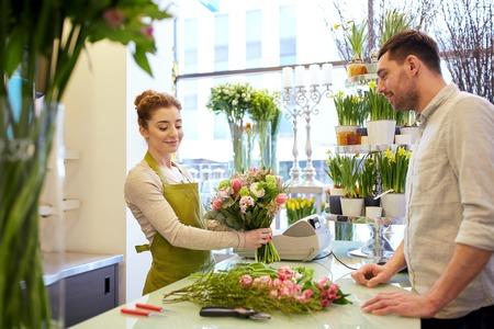 floristry: people, shopping, sale, floristry and consumerism concept - happy smiling florist woman making bouquet for and man or customer at flower shop Stock Photo