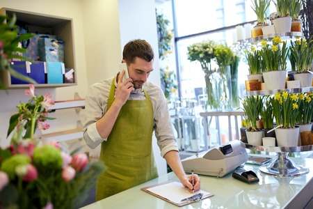 people, sale, retail, business and floristry concept - happy smiling florist man calling on smartphone and making notes to clipboard at flower shop counter Zdjęcie Seryjne
