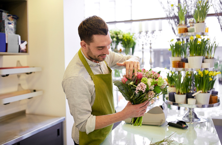 floristry: people, business, sale and floristry concept - happy smiling florist man making bunch at flower shop