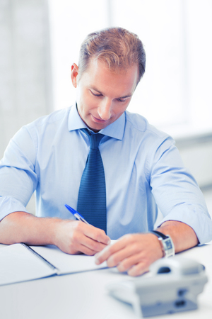 making notes: business concept - handsome businessman working in the office Stock Photo