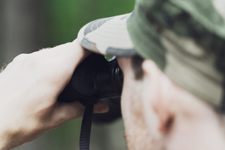 hunting, war, army and people concept - close up of young soldier, ranger or hunter with binocular observing forest Stock Photo