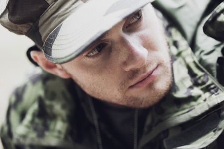 offensive: war, army and people concept - close up of young soldier in military uniform