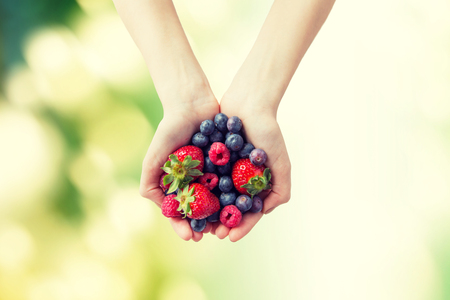 healthy eating, dieting, vegetarian food and people concept - close up of woman hands holding different ripe summer berries over green natural background