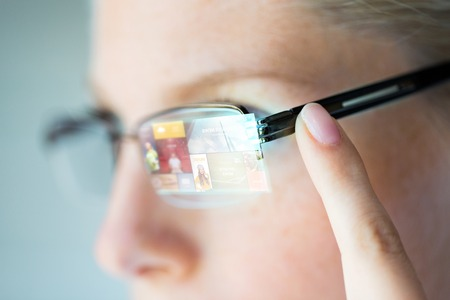 earpiece: business, media, future technology, information and people concept - close up of woman in eyeglasses with virtual screen projection pointing finger to earpiece