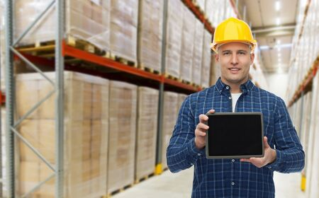 business services: wholesale, logistic, business, export and people concept - happy man or manager showing tablet pc computer blank screen over warehouse background Stock Photo