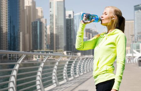 water sports: fitness, sport, people and healthy lifestyle concept - woman drinking water after doing sports over dubai city street or waterfront background