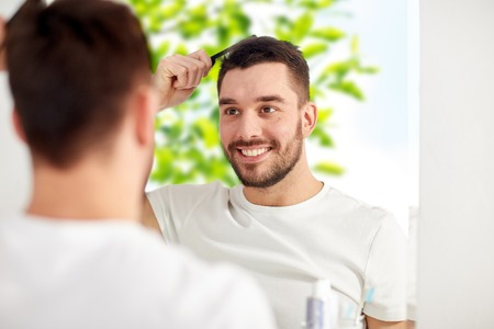 beauty, grooming and people concept - smiling young man looking to mirror and brushing hair with comb at home bathroom over green natural background Foto de archivo