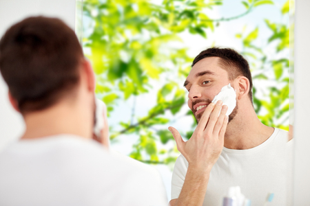 natural looking: beauty, hygiene, shaving, grooming and people concept - smiling young man looking to mirror and applying shaving foam to face at home bathroom over green natural background
