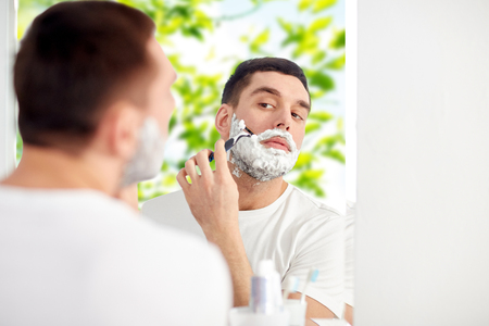 natural looking: beauty, hygiene, shaving, grooming and people concept - young man looking to mirror and shaving beard with manual razor blade at home bathroom over green natural background Stock Photo