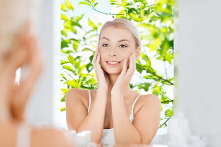 natural looking: beauty, hygiene, morning and people concept - smiling young woman looking to mirror at home bathroom over green natural background Stock Photo