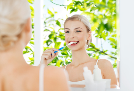 health care, dental hygiene, people and beauty concept - smiling young woman with toothbrush cleaning teeth and looking to mirror at home bathroom over green natural background Фото со стока