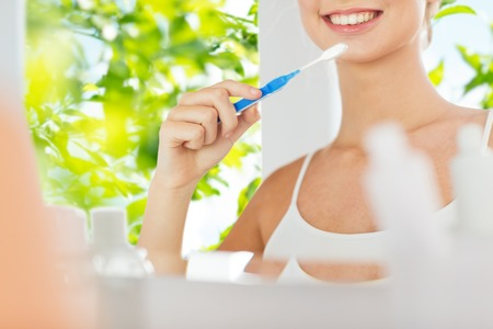 health care, dental hygiene, people and beauty concept - close up of smiling young woman with toothbrush cleaning teeth and looking to mirror at home bathroom over green natural background Stock Photo