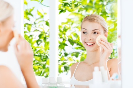hygienic: beauty, skin care and people concept - smiling young woman washing her face with facial cleansing sponge at bathroom over green natural background