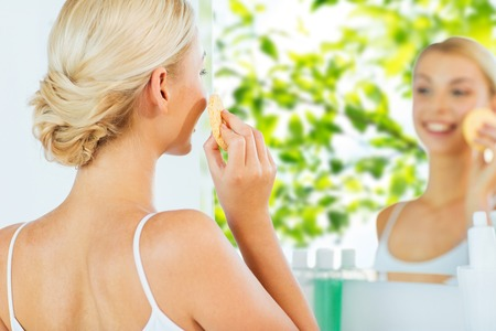 purifying: beauty, skin care and people concept - close up of smiling young woman washing her face with facial cleansing sponge at home bathroom over green natural background