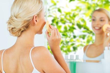 masaje facial: belleza, cuidado de la piel y el concepto de la gente - cerca de la mujer joven sonriente que se lava la cara con la esponja de limpieza facial en el cuarto de baño en casa sobre fondo verde natural Foto de archivo