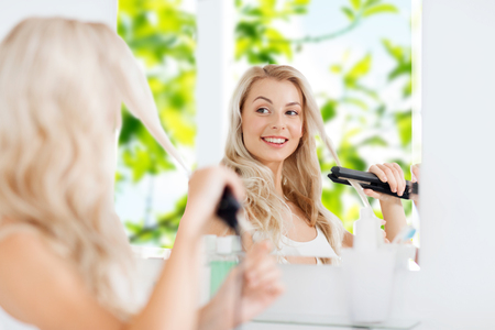 woman hairstyle: beauty, hairstyle, morning and people concept - smiling young woman with styling iron straightening her hair and looking to mirror at home bathroom over green natural background