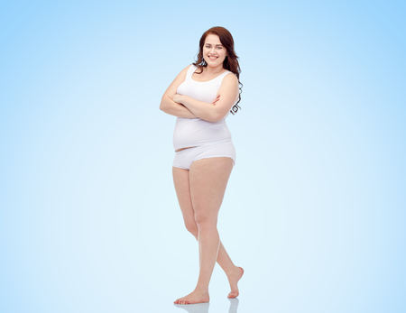 plus size and people concept - happy plus size woman in underwear over blue background