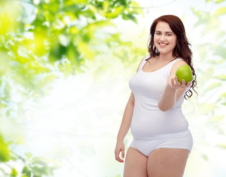 woman underwear: weight loss, diet, slimming, healthy eating and people concept - happy young plus size woman in underwear with green apple over natural background Stock Photo