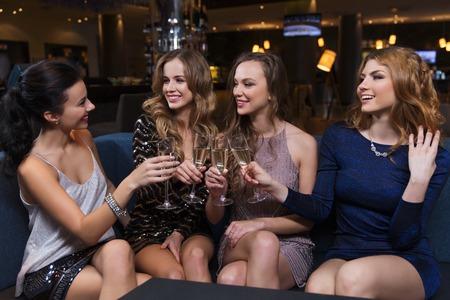 mujeres felices: celebración, amigos, despedida de soltera y concepto de vacaciones - mujeres felices tintineo de copas de champán y que celebran en el club nocturno